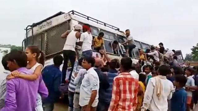 Locals rescue passengers from bus stuck on flooded bridge