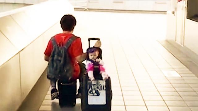 Easy riders! Dad takes the strain out of travelling by driving a MOTORISED suitcase and towing his b