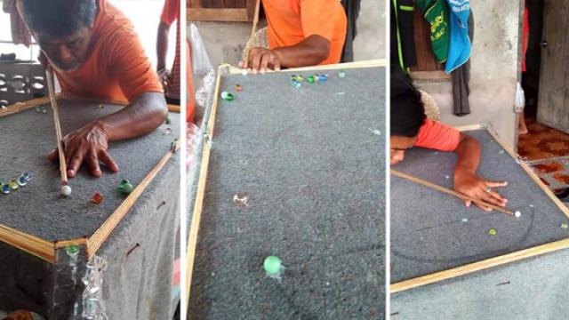 Man creates homemade billiard where pockets are plastic bottle caps and balls are marbles