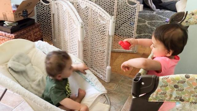 Adorable moment twins separated for being naughty find way to still share toys