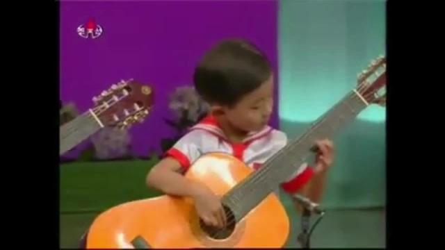 Playing the guitar that is bigger than the body, but the five little babies still play the instrumen