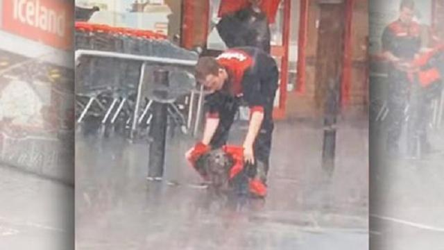 A Good Man Covers A Little Dog Using His Coat In A Rainy
