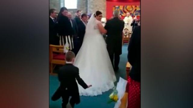 Bride Walks Down Aisle When Nephew Runs Up Behind Her Making Guest Gasp Doing The Unthinkable