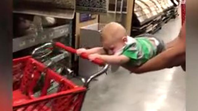 This isn't his impression of Superman, he refuses to let go of the cart!