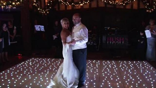 Newlyweds pose on twinkling dance floor, but the moment isnt serene for very long.