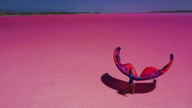 Woman kitesurfing across spectacular pink lagoon has to be