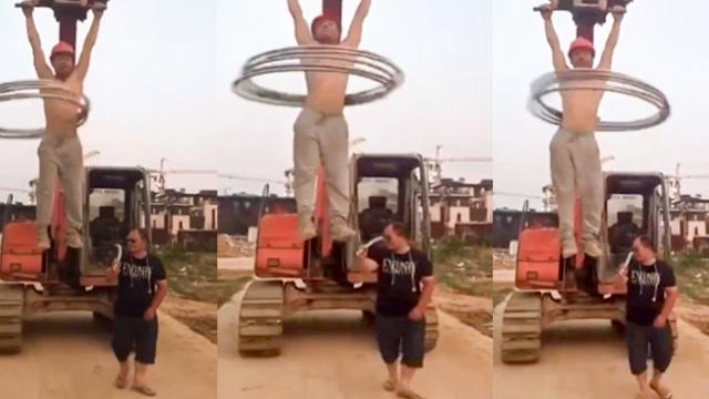 Worker does pull-ups on moving digger while performing hula hoop tricks