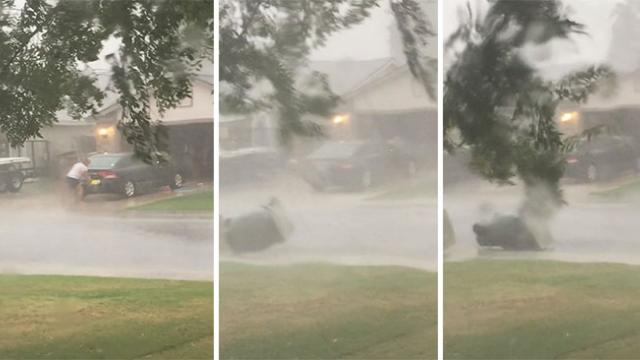 Guy washes his car in the middle of a rainstorm