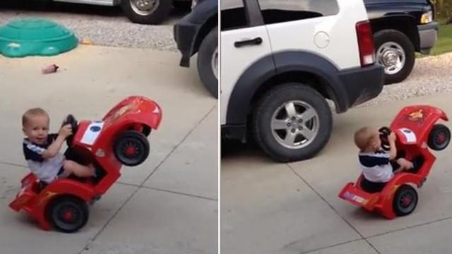 Daredevil Baby Stares At Camera While He Pops A Power Wheels Wheelie_Large