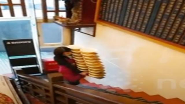 Nothing is impossible Skilled Chinese waitress carries 20 bowls of hot noodles up flight of stairs