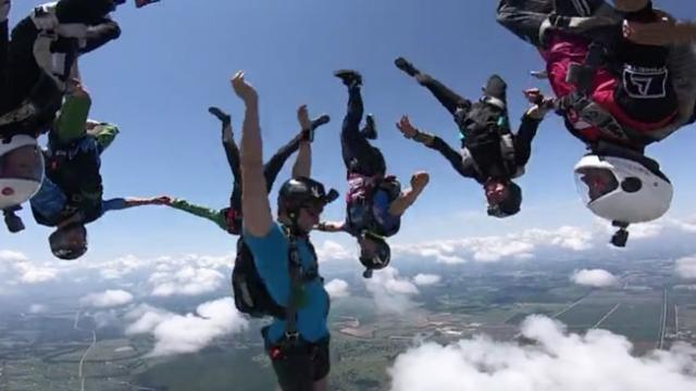 Fearless skydivers plummet head first towards the ground during epic mid-air trickshot