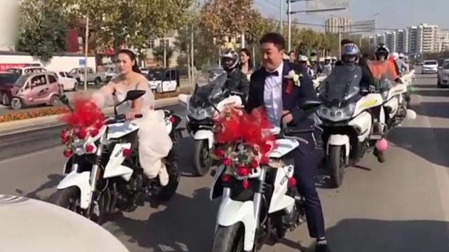 Beautiful bride rides large engine motorbike making passersby surprised