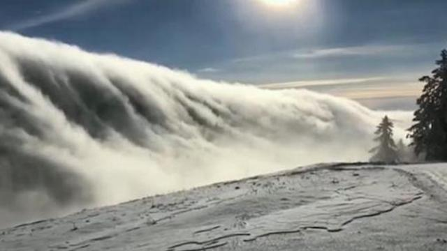 Impressive Wave of Fog Rolls Over Mountain Range in