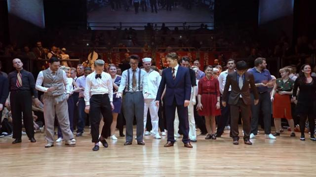 Dozens Of Dancers Line Up & Launch Into Fancy Swing Routine That'll Make Your Head Spin.