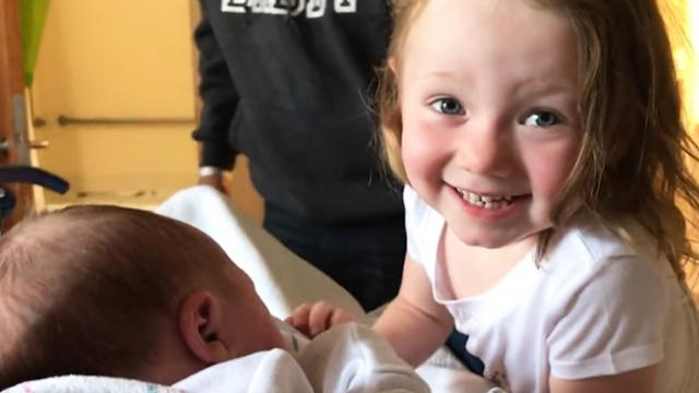 Adorable moment toddler falls in love with newborn baby sister after meeting her for the first time