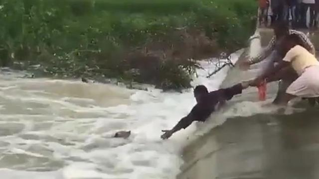 Suspenseful footage of brave rescuers trying to rescue dog trapped in flood