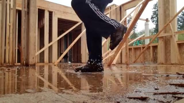 Construction Worker Dances In The Rain To The Delight Of Coworker
