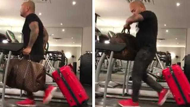 Man prepares for trip by running on treadmill with luggage