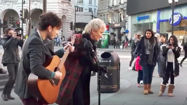 Pedestrian Grabs Street Musicians Mic — Crowd Cheers When They Realize Who He Is.